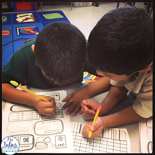 two boys working on a number of the day worksheet during math centers