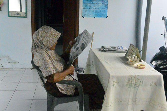 Pemilik homestay sedang membaca koran di pagi hari