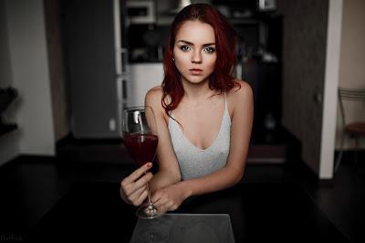 Linda chica pelirroja tomando vino sentada