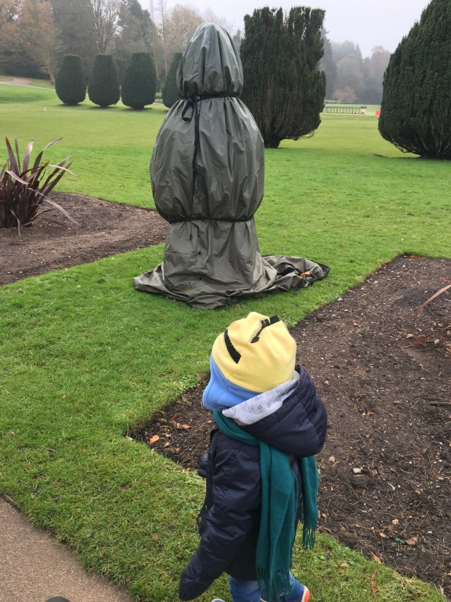 12-days-of-christmas-at-dyffryn-gardens-a-toddler-explores-a-statue-wrapped-for-the-winter