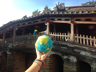 hand holding out a knitted globe with a old stone arched, roofed bridge; the roof is decorated with dragons and red circles