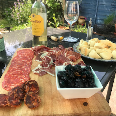 An array of cheese, meats and olives on a wooden board. There are glasses of wine in the background.