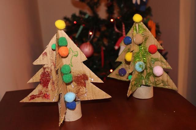 pequenas árvores de Natal, feitas em cartão e decoradas por crianças, com marcadores e pompons coloridos
