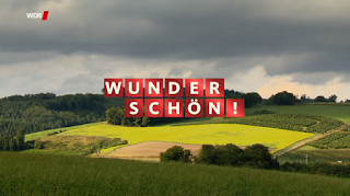 """Eine Berglandschaft mit gelben Feldern, darübergelegt der Schriftzug der Sendung """"Wunderschön"""". Weiße Buchstaben auf rotem Grund"""
