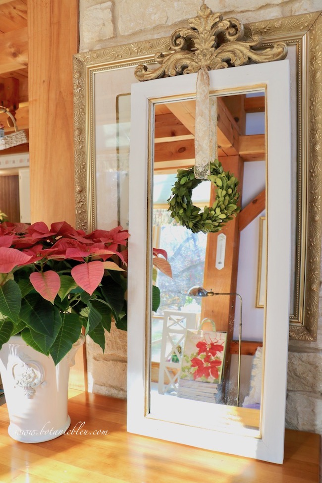 French country mirror decorated for Christmas with a small boxwood wreath hanging from a gold and white fleur de lis ribbon