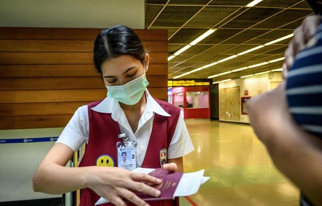 Trong ảnh: Nhân viên kiểm tra hộ chiếu của một hành khách tại sân bay Don Mueang ở Bangkok, Thái Lan ngày 21-1-2020. (Ảnh: AFP/TTXVN)