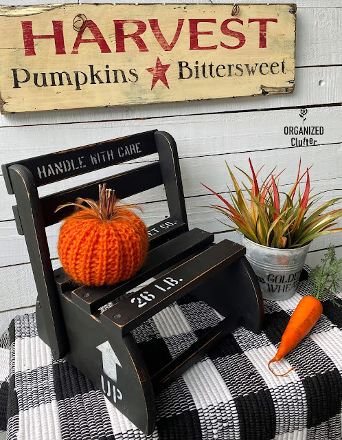Photo of an upcycled folding step stool/chair staged with fall decor