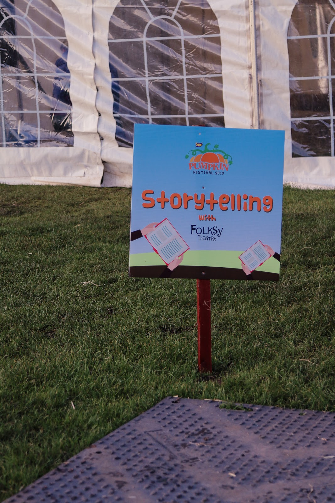"Close up of the blue and ornage sign that has ""storytelling"" written on it in orange writing outside a big white tent"
