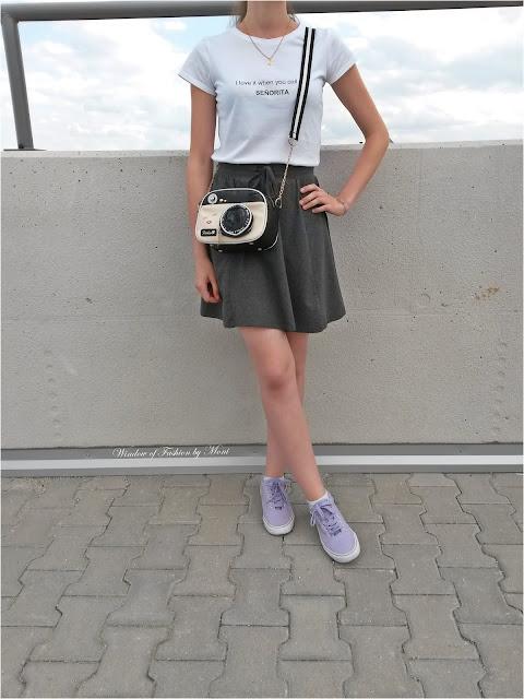 Biały T-shirt z napisem, szara spódniczka, fioletowe tenisówki, torebka aparat, bransoletka z koniczynką