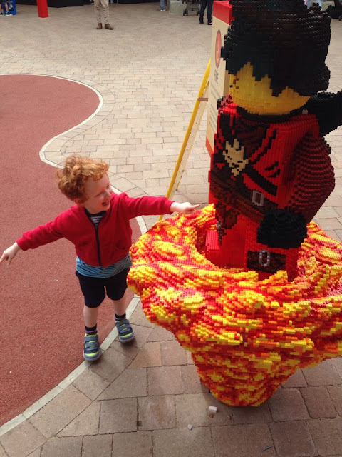 Large Lego Ninjago figure with smiling little boy at the side of it