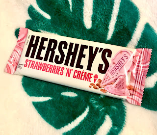 A rectangular pale pink rectangular chocolate bar with little white sugar crystals running throughout in a white rectangular packet with Hersheys in bold black font with strawberries and creme underneath in pink small font on a bright background