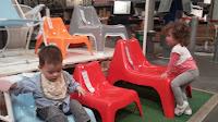 Деца се катерят на столчетата, изложени в мебелния магазин.