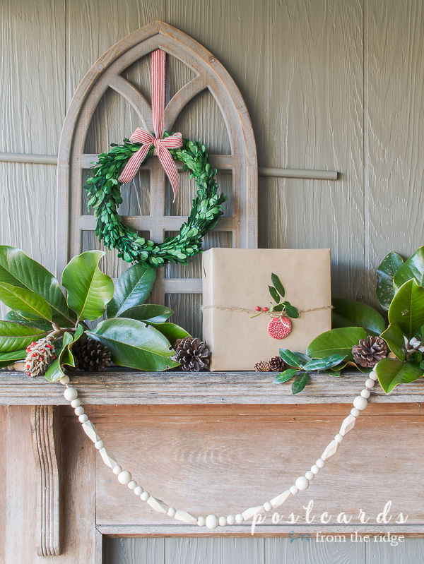 arched wooden cathedral window frame with preserved boxwood wreath on outdoor vintage mantel