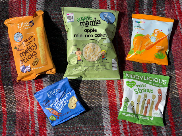 A selection of bags of baby snacks from the supermarket including Ella's Kitchen, Aldi Mamia, Kiddylicious and Lidi Lupilu