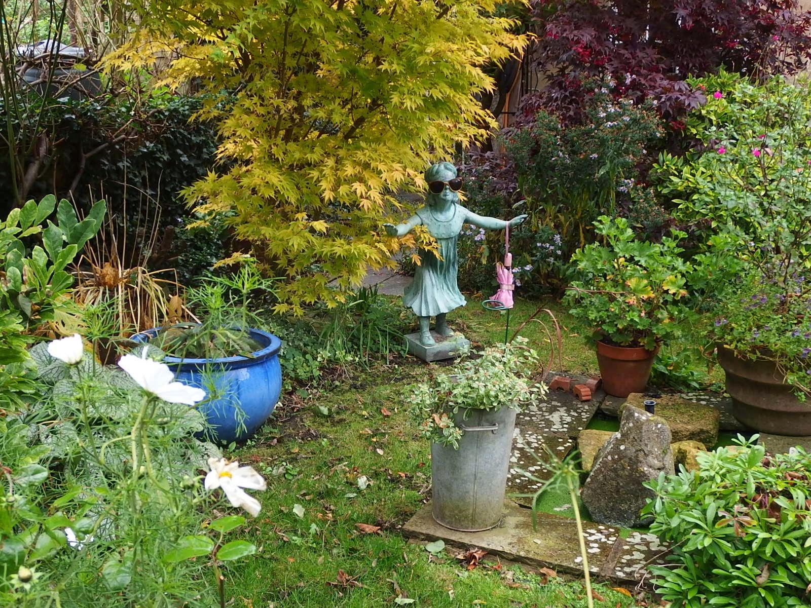 Photo of a front garden in Wiltshire with a statue of a girl dressed for the season