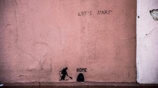 """Graffiti Text """"Let's Start"""" oben, unten am Boden ein kleines schwarzes Mauseloch überschrieben mit """"Home"""", jemand ist gerade dabei zu schaufeln"""