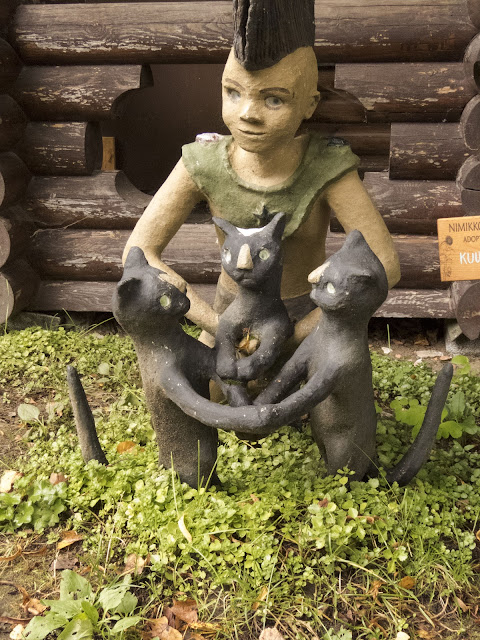 Kid with a mohawk and 3 cats at Parikkala Sculpture Park in Finland