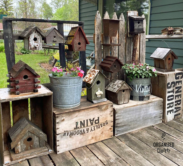 Photo of rustic birdhouses and buckets of annuals displayed on old crates