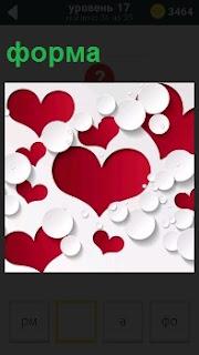 Вырезанные формы в качестве трафарета в виде сердечка на красном фоне