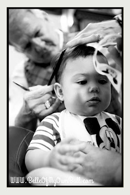 A photo of a baby playing with stickers while receiving his first haircut at Harmony Barber Shop in the Magic Kingdom.
