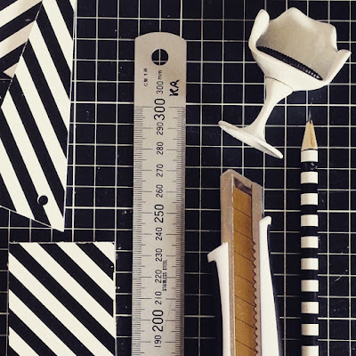 Flat lay of a pencil, utility knife, metal ruler and a one-twelfth scale modern miniature tulip chair along with a rectangle of black and white striped wood, plus some offcuts.