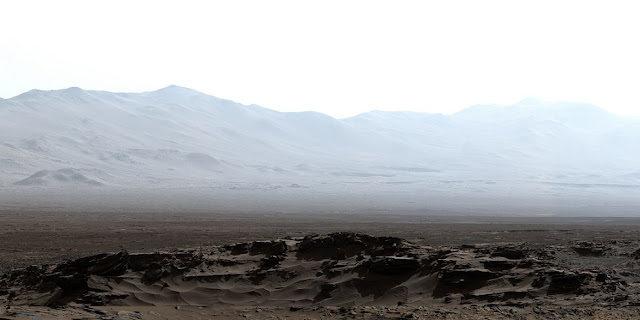 This early-morning view from the Mast Camera (Mastcam) on NASA's Curiosity Mars rover covers a field of view of about 130 degrees of the inner wall of Gale Crater. It was acquired during a period when there was very little dust or haze in the atmosphere, so conditions were optimal for long-distance imaging. The right side of the image fades into the glare of the rising sun. Credit: NASA/JPL-Caltech/MSSS