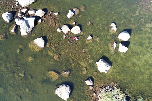 Ilmakuvassa pieni hahmo snorklaa valtavien lohkareiden välissä