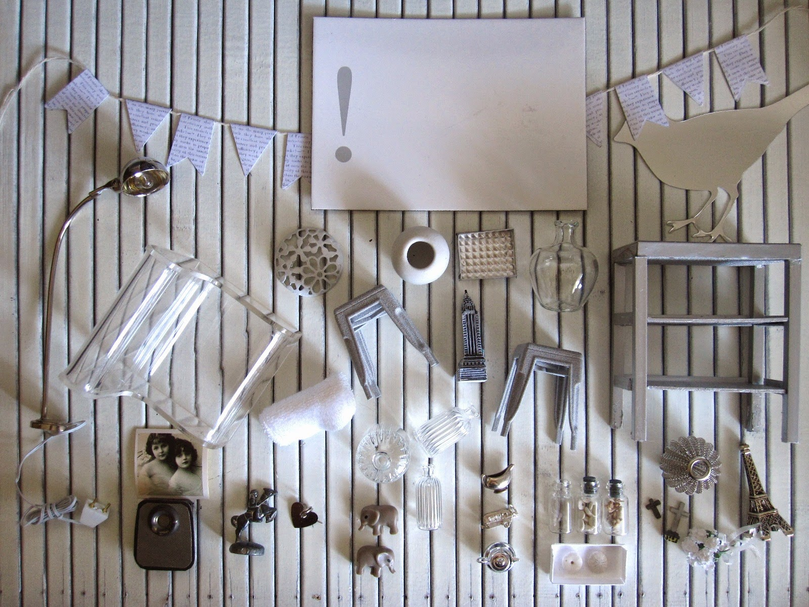 Selection of grey and white modern dolls' house miniatures arranged on  white-painted wood panelling.