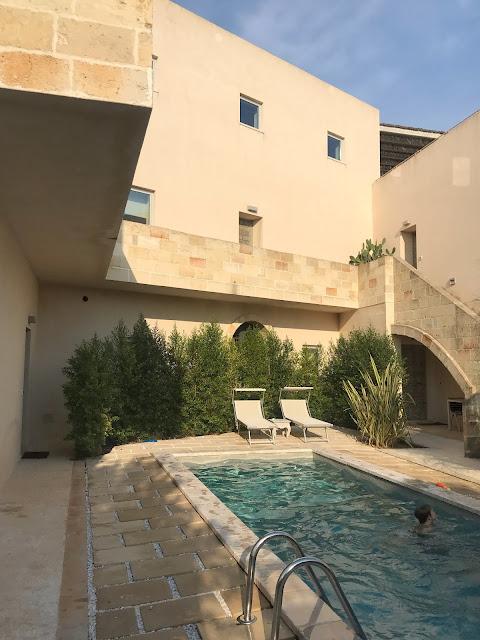 Patio del edificio de piedra color arena con piscina en el centro