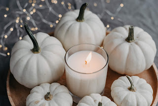 white candle displayed with white pumpkins - interior design