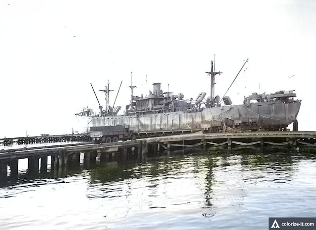 A ship docked at the newly reconstructed pier.  Image source:  United States National Archives.  Colorized courtesy of Algorithmia.