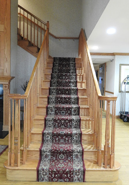 An oak staircase with landing and upper stairs and a carpet runner.
