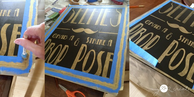 putting a boarder on the selfie sign using scotch blue painter's tape
