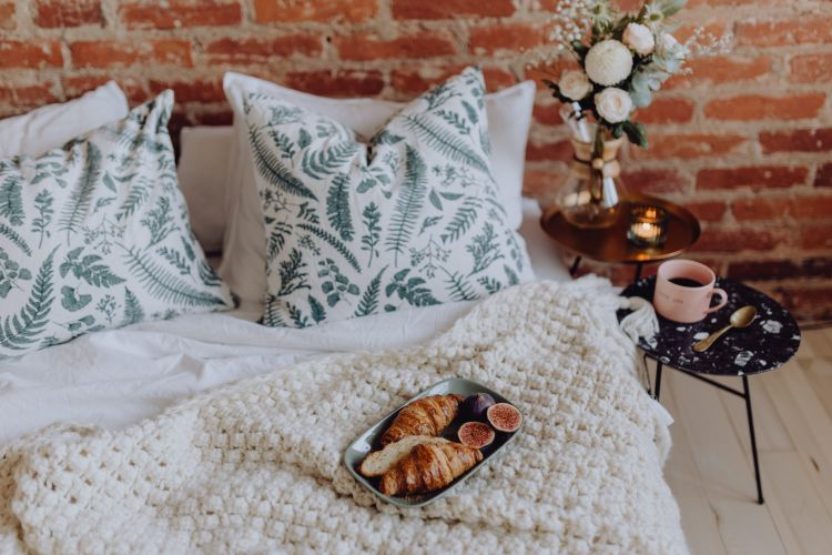 cosy bedroom with a bed and pastries for breakfast