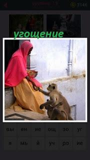 женщина угощает обезьяну бананами на ступеньках дома
