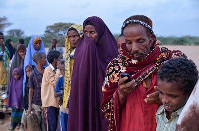 Using his cell phone in Dadaab, Kenya.