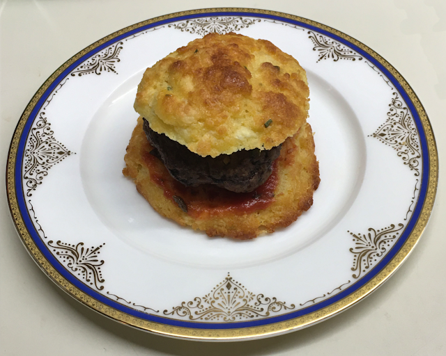 Photo of hamburger on a biscuit, served on a plate
