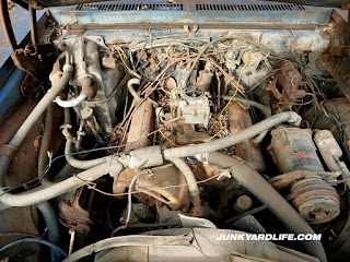 Straight on shot under hood looking at dingy, brown 307-V8 of the 1970 Nova.