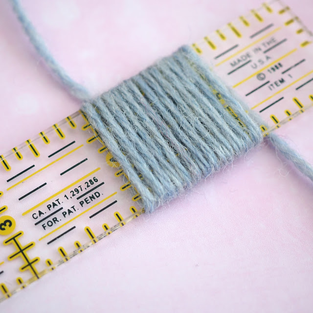 pale blue yarn wrapped around an inch of a ruler