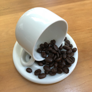 coffee beans pouring from an espresso cup