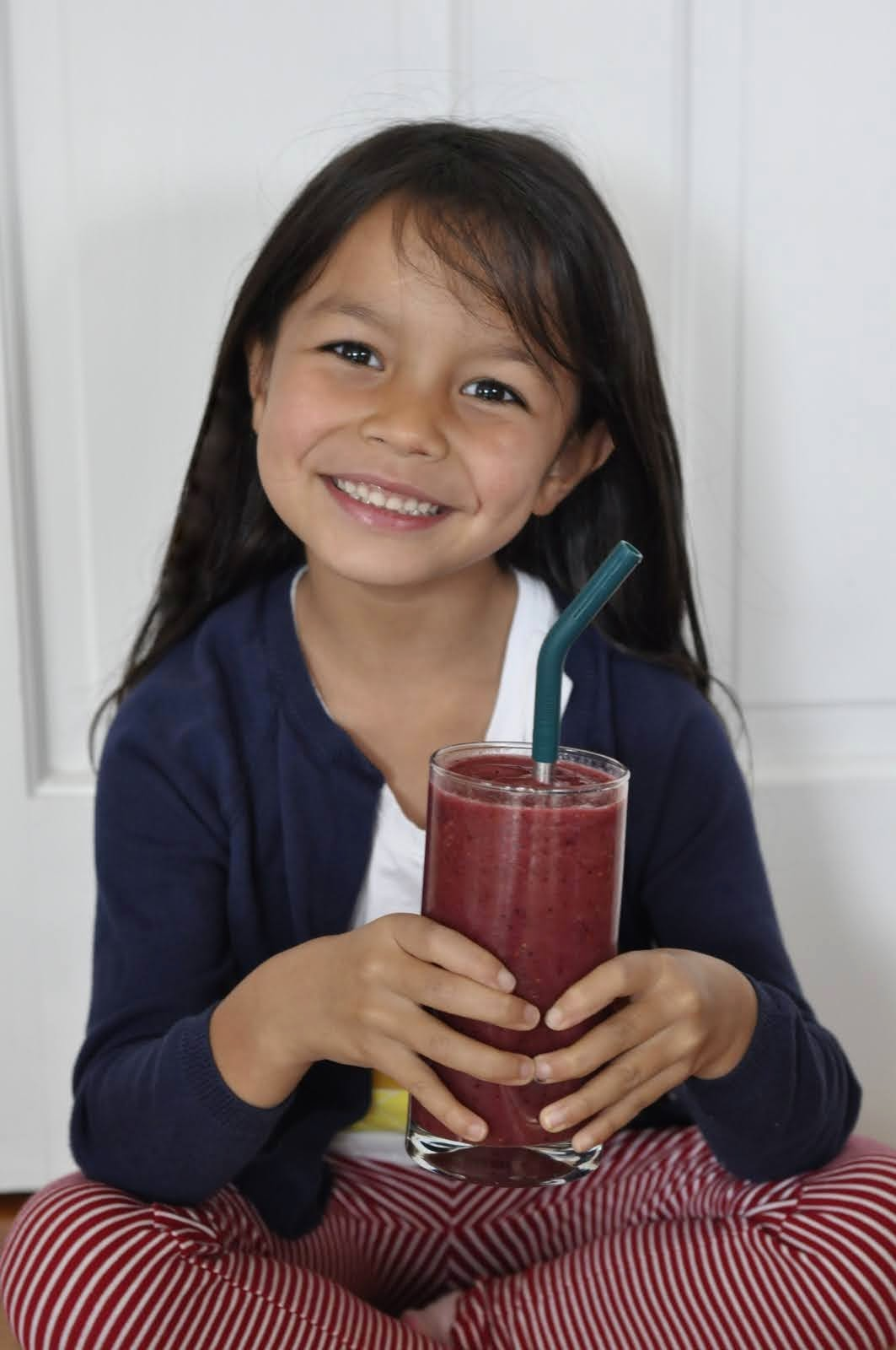 Young child with long brown hair holds a glass with a Simple Mixed Berry Smoothie in it. The glass also has a metal straw to make sipping a lot easier.