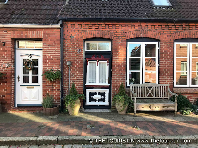 Redbrick house with an ornately painted door, a wooden bench in front of the house.