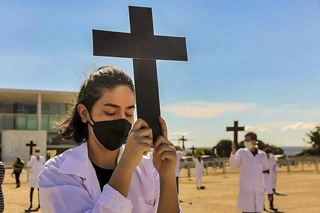 Em silêncio e segurando cruzes