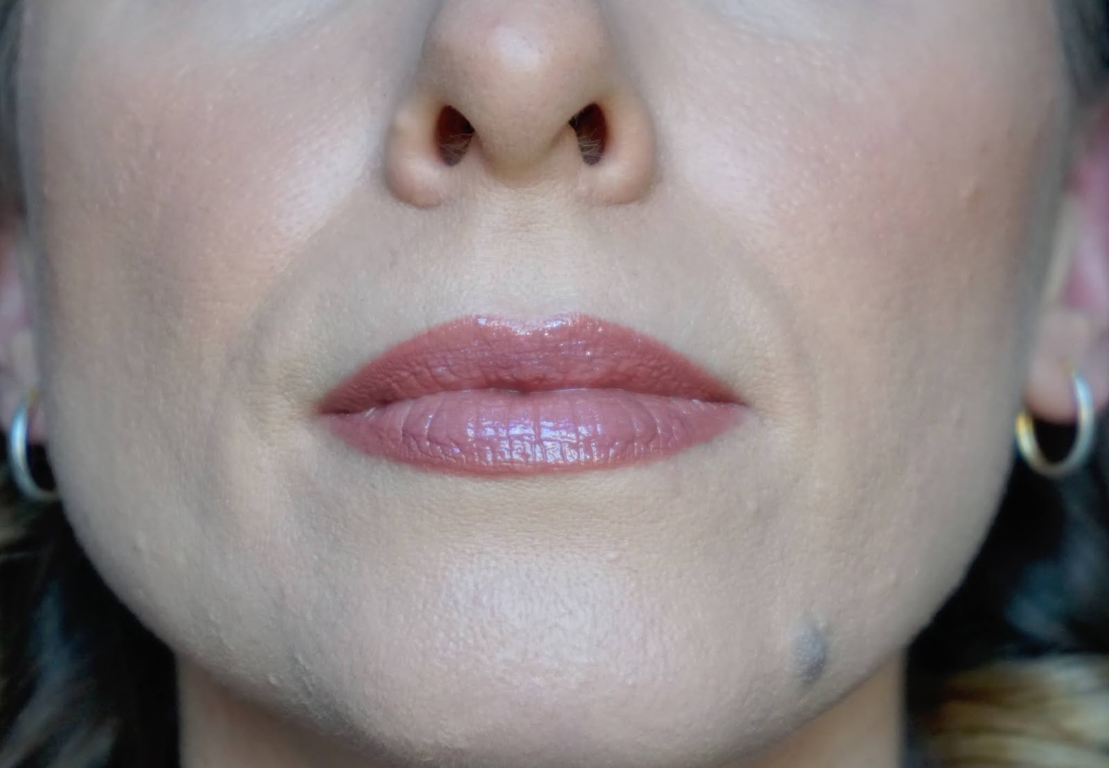 Half of face with lipstick and lip gloss applied to lips
