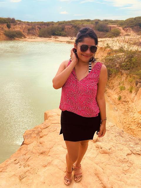 mulher morena, jovem, cabelo preto, oculos escuros, blusa rosa e saia preta com a paisagem de uma lagoa verde ao fundo