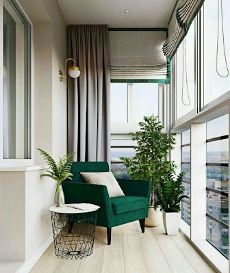 Simple apartment balcony design with emerald green chair and plants decoration