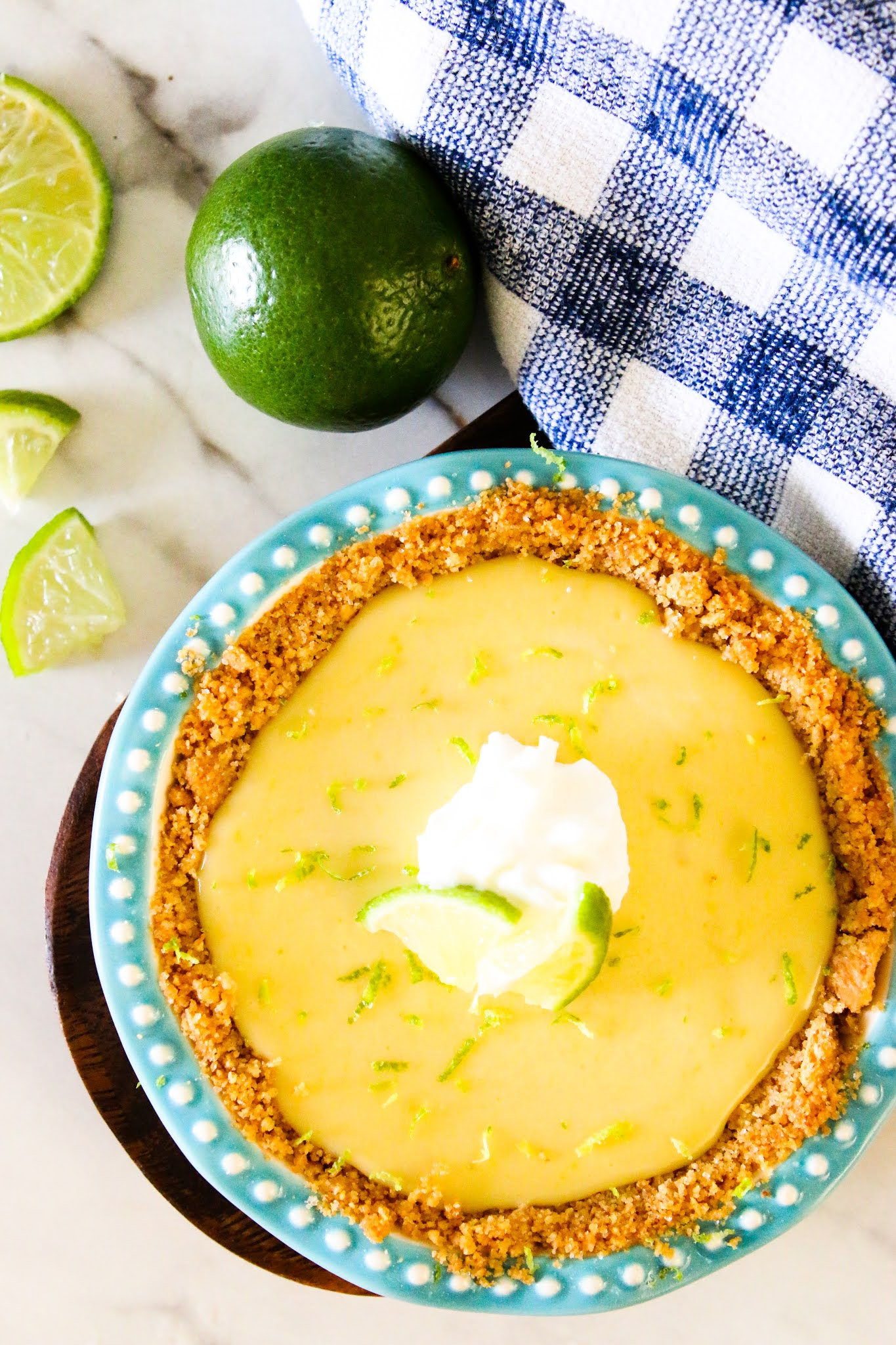Key lime pie in a blue pie plate on a wood platter with cut limes on a marble table and a blue dish towel in the background.
