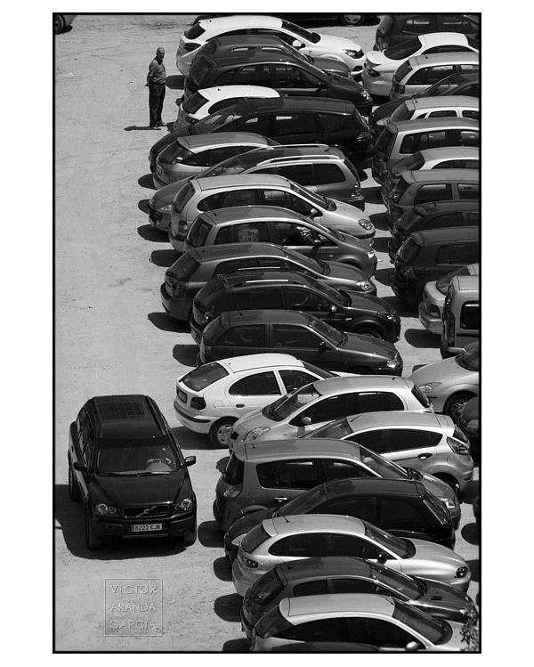Fotografía en blanco y negro de muchos coches aparcados en un solar.