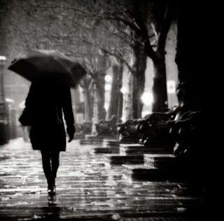 perempuan berjalan di tengah hujan