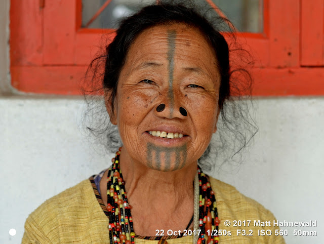 matt hahnewald photography; facing the world; character; face; tattoo; face tattoo; tribal tattoo; eyes; nose; nose plugs; facial expression; eye contact; consent; empathy; emotion; respect; ethnic; traveling; tribal; adivasi; rural; village; traditional; cultural; hong; ziro; arunachal pradesh; northeast india; asian; indian; apatani; one person; female; adult; elderly; woman; picture; photo; illustrative editorial; face perception; physiognomy; educational; nikon d3100; nikkor af-s 50mm f/1.8g; prime lens; 50mm lens; nifty fifty; 4x3 aspect ratio; horizontal orientation; street; portrait; closeup; headshot; seven-eighths view; outdoors; color; posing; authentic; unique; yaping hullo; yesso; shutterstock; smiling; teeth; rapport